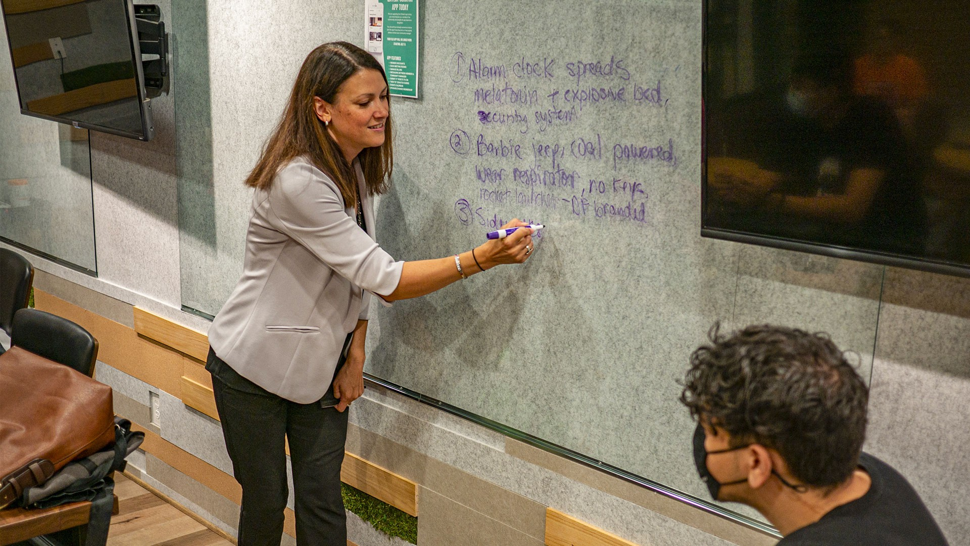 Presenter writing on a dry erase wall