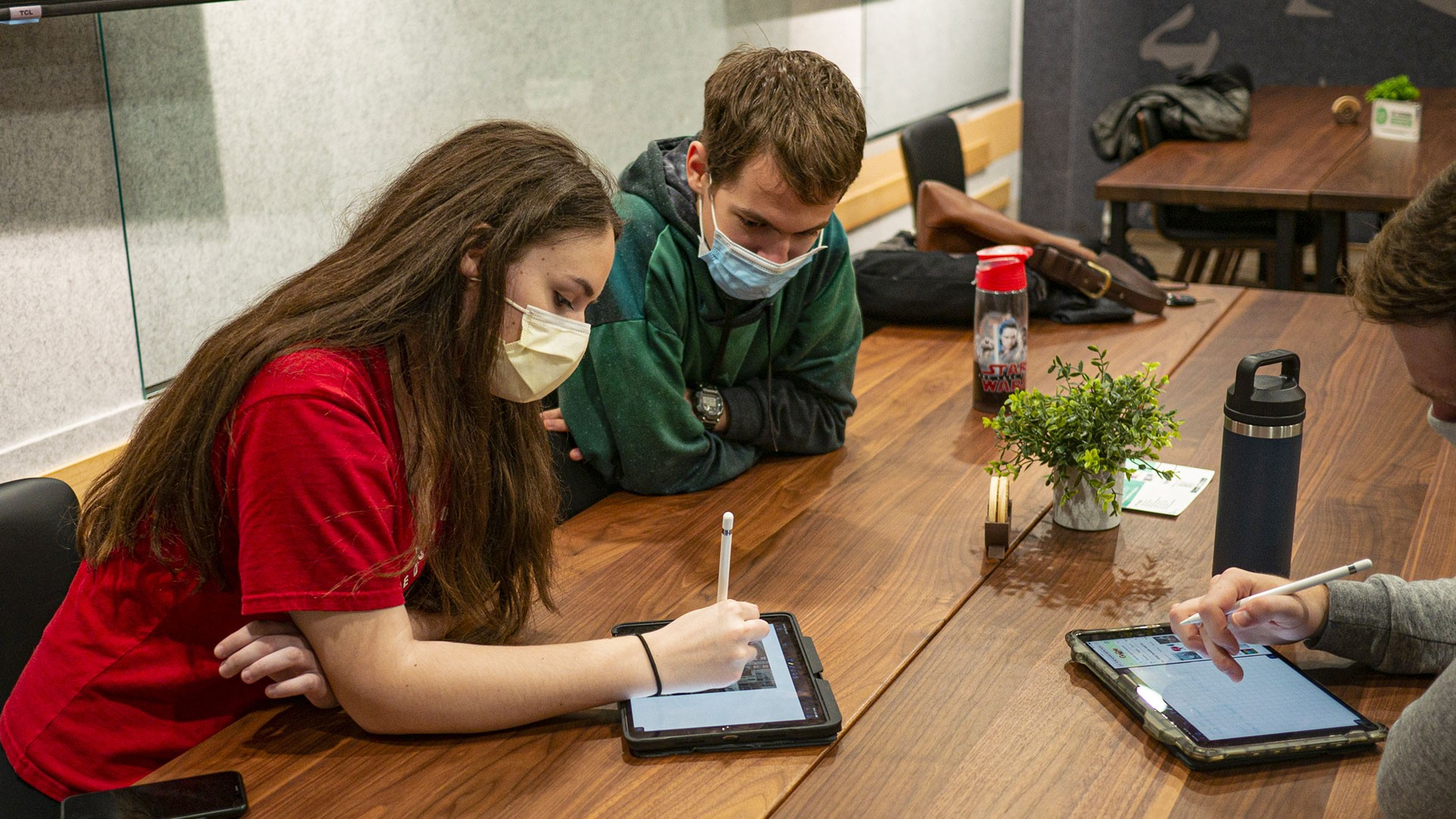 Students sitting at a table using iPads together