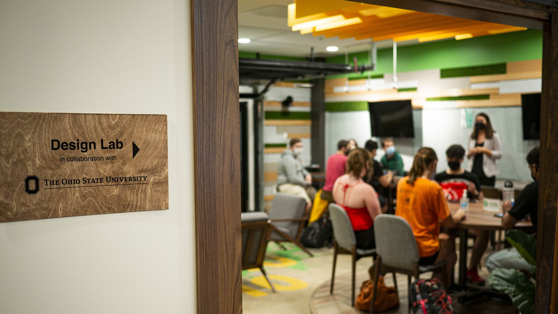 Close up a sign by an open door that reads Design Lab in collaboration with The Ohio State University and a workshop with a group of people is happening inside