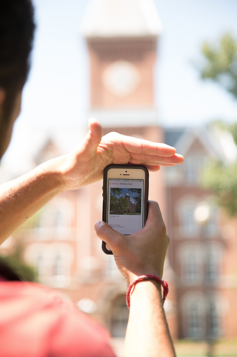 male hands holding iPhone showing university app