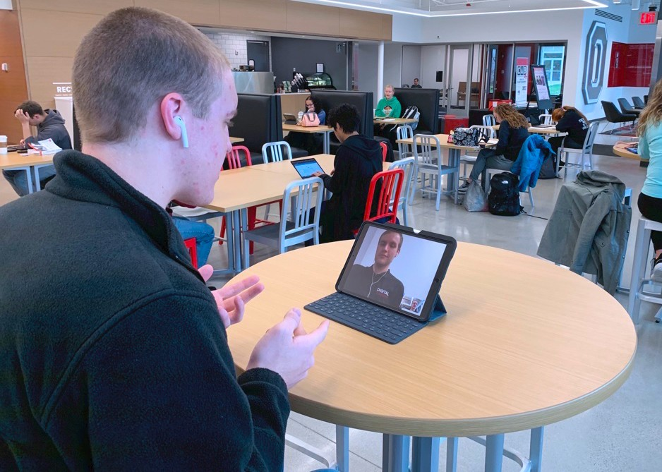 A person looking at a video call on an iPad.
