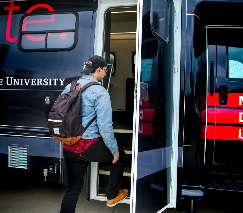 Student steps up into the open bus doorway