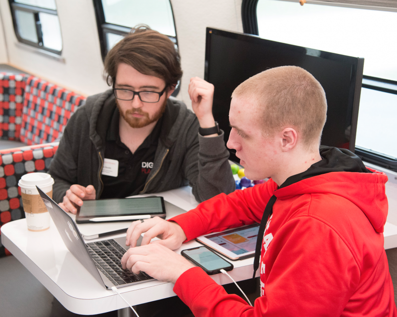 Student and instructor work together on laptop